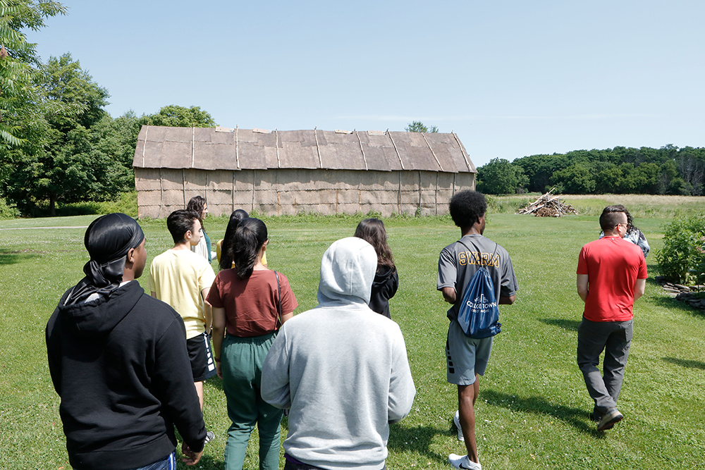 group of students waking toward a Native American longhouse