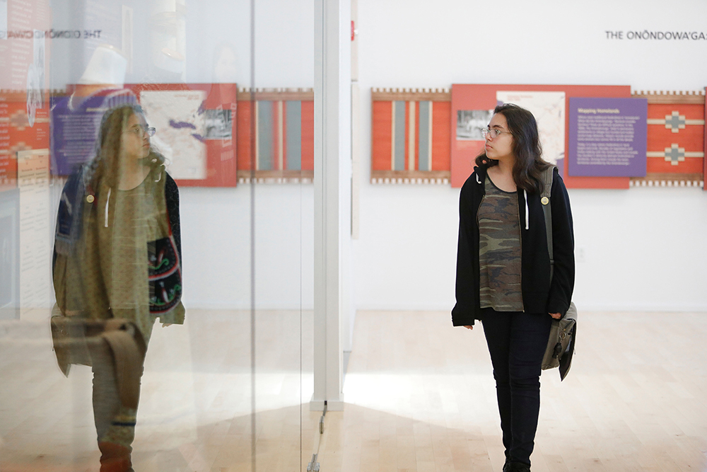 student walking through an art exhibit is reflected in the exhibit's glass walls.