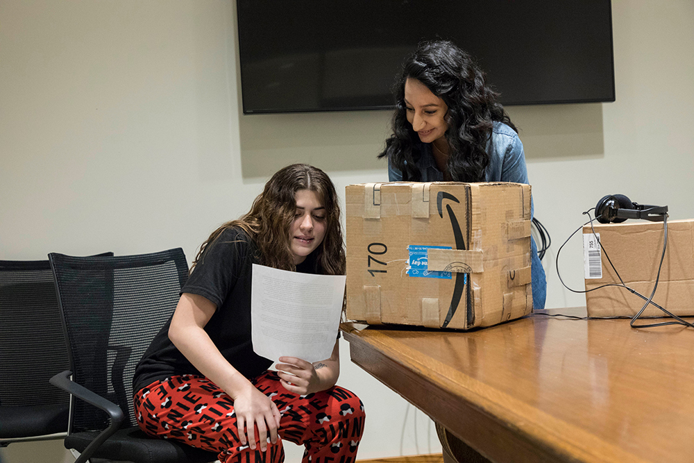 two students reading a script into a microphone and using a cardboard box to muffle the sound.