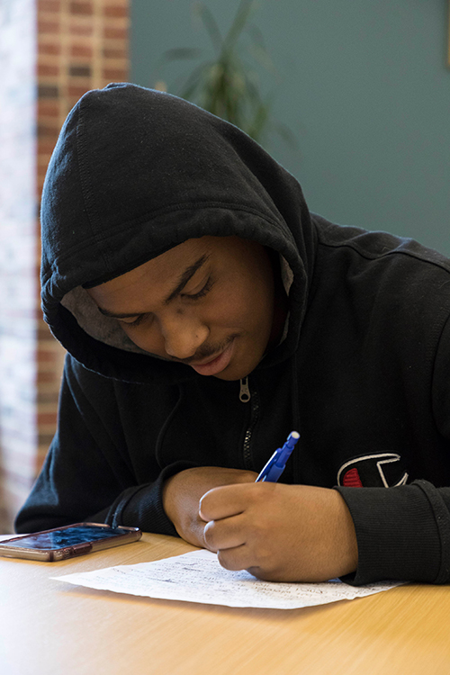student at a desk, writing on a piece of paper.