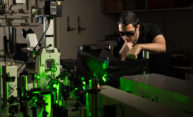 researcher in safety glasses working in an optics lab.