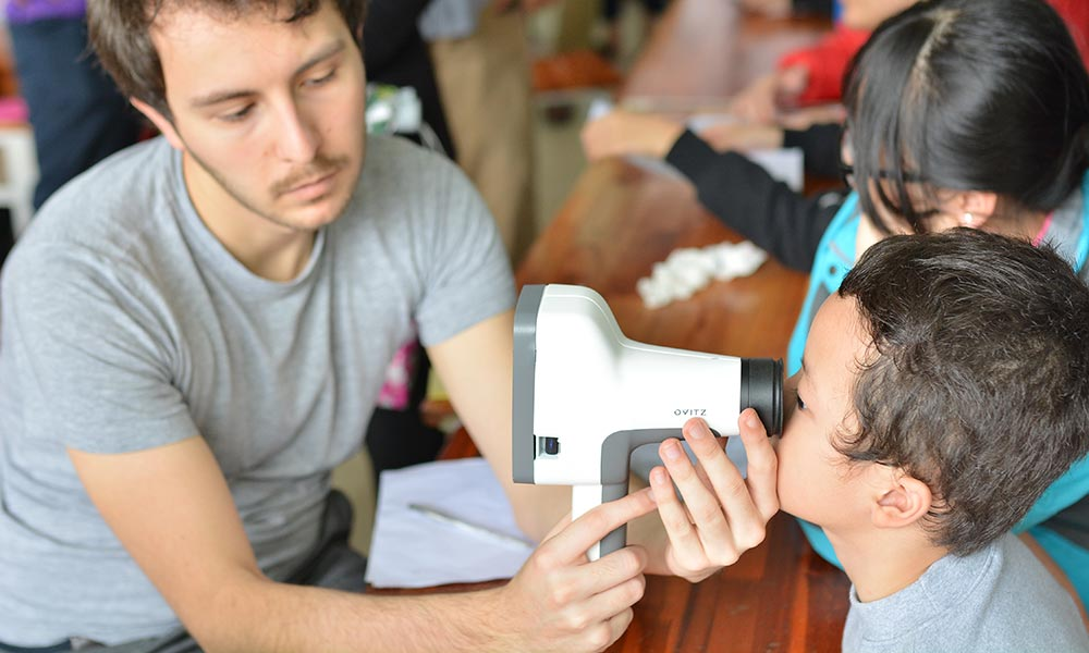 technician holds a device in front of the eyes of a young child, who looks through the device