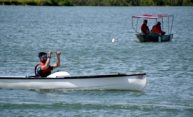 student pilots a small boat covered in solar panels on a lake during a race