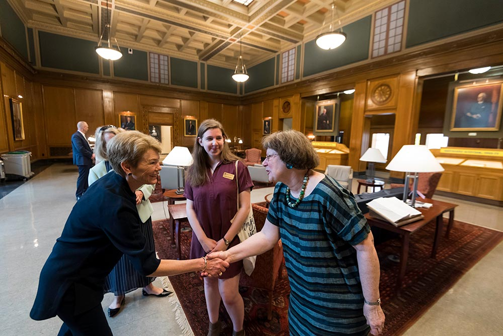 Sarah Mangelsdorf shaking hands with Joan Rubin as others look on in a beautiful library setting.