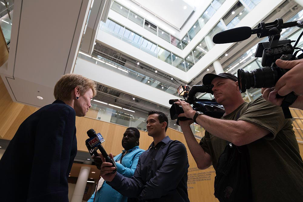 Sarah Mantgesdorf surrounded by reporters with microphones and cameras.