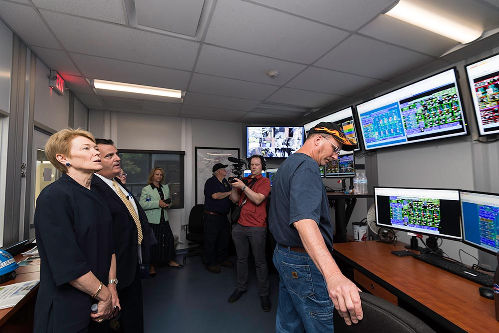 group of people in a control room looking at data on a bank of large computer screens.