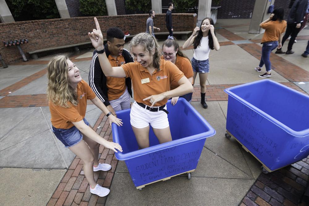 students dancing in blue wheelie bins.