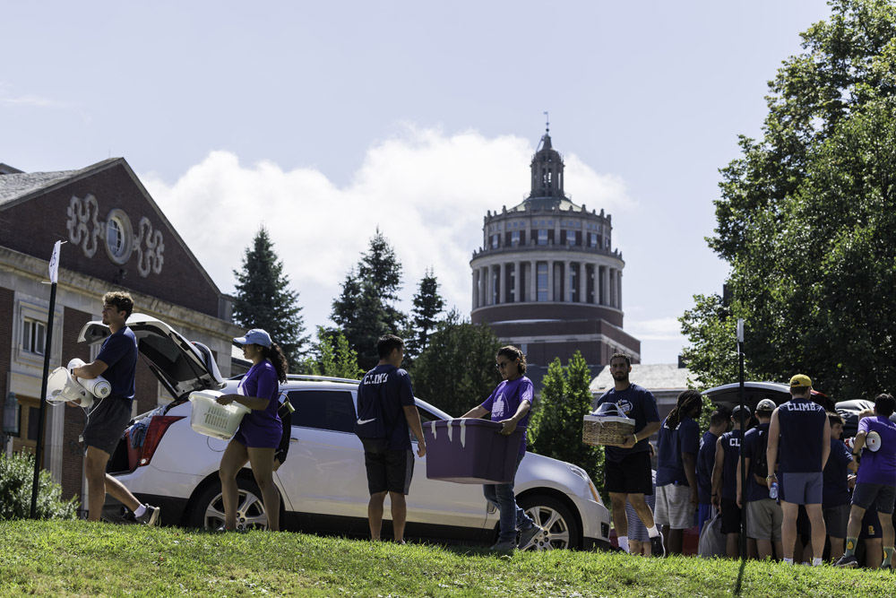 large group of students unloading cars in front of Rush Rhees Library.