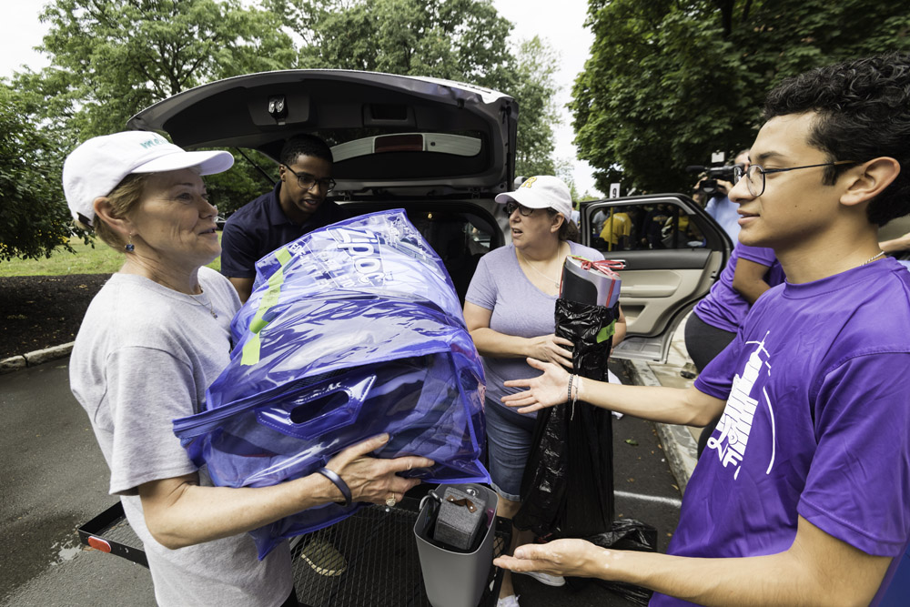 President Mangelsdorf lifts boxes from a student's car.