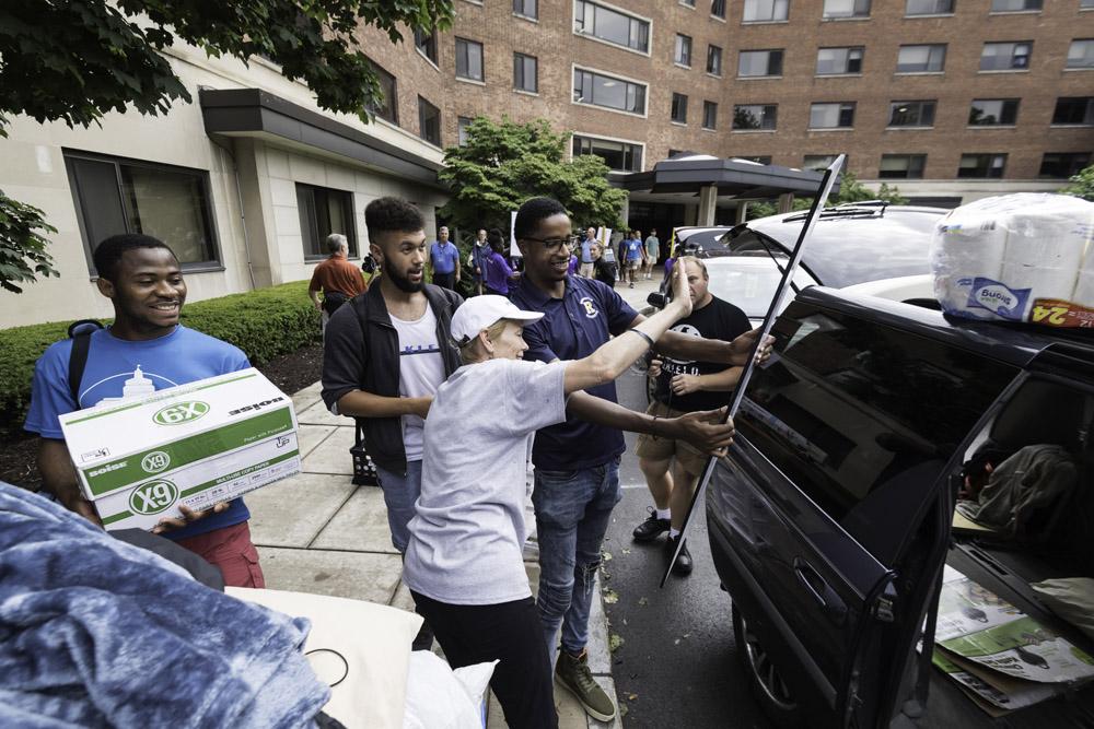 President Mangelsdorf and SA president Jamal Holtz wave toward a family's car.
