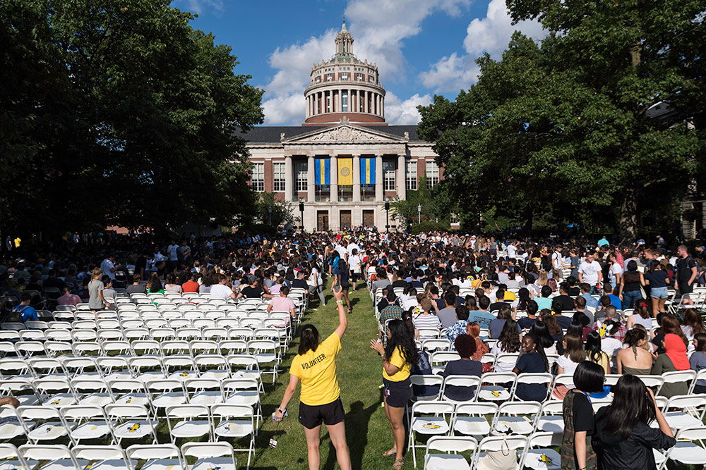 chairs on the quad with the library in the background as students process in