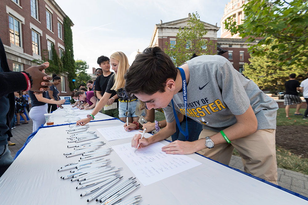 student line up at a table to sign the class roll