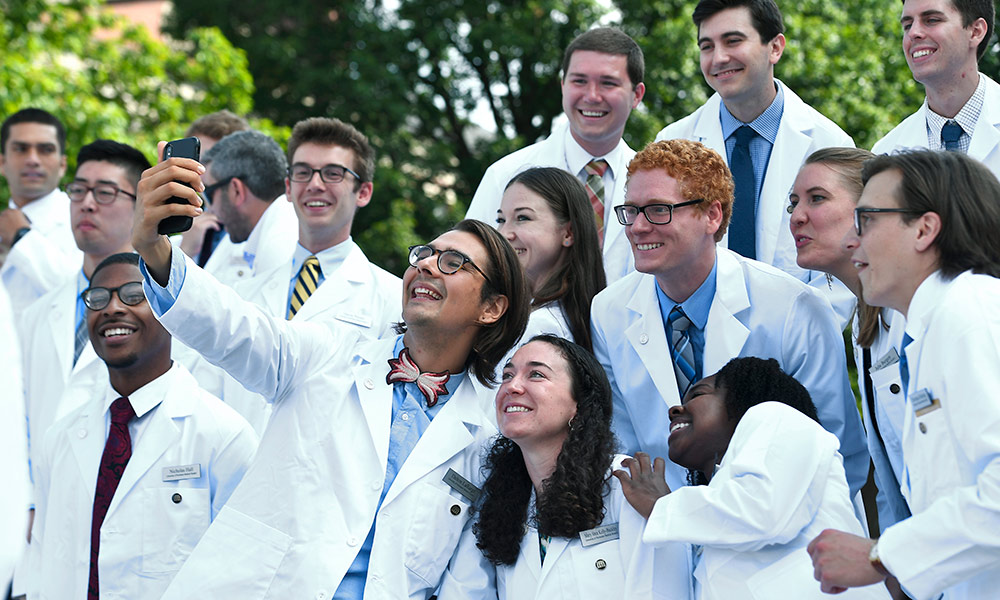 large group of medical students in white lab coats pose for photos and take selfies