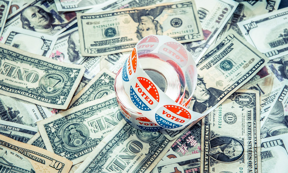 Roll of I VOTED stickers sits atop a pile of dollar bills to illustrate money in politics.