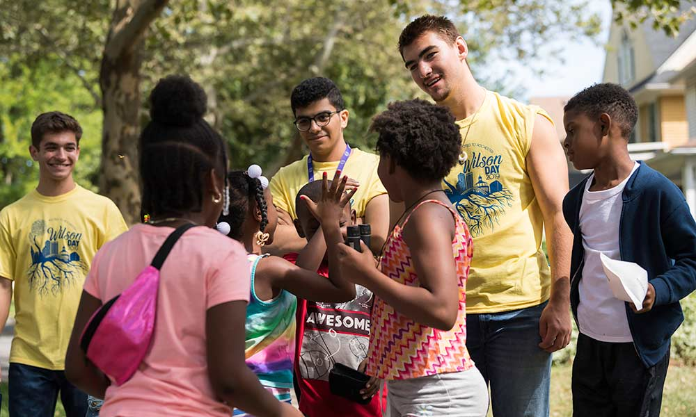group of college students in matching t-shirts giving kids high-fives