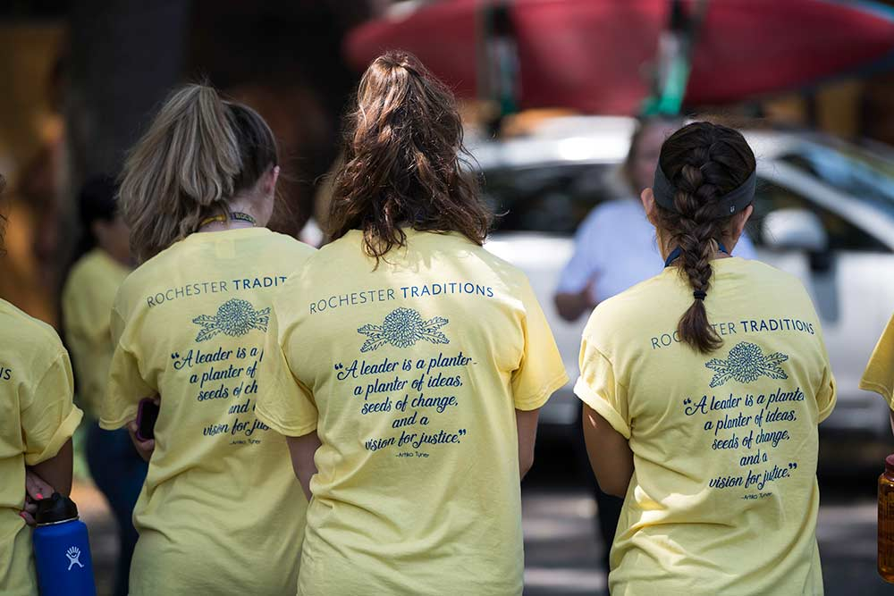 three people wearing t-shirts that read ROCHESTER TRADITIONS. A LEADER IS A PLANTER, A PLANTER OF IDEAS, SEEDS OF CHANGE, AND A VISION FOR JUSTICE. -- ARTIKA TYNER