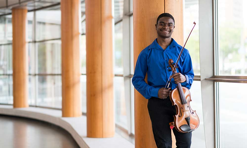 violist smiles while leaning against an auditorium wall.