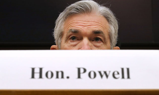 Jerome Powell sits at a congressional hearing behind a photo of a sign that reads HON. POWELL