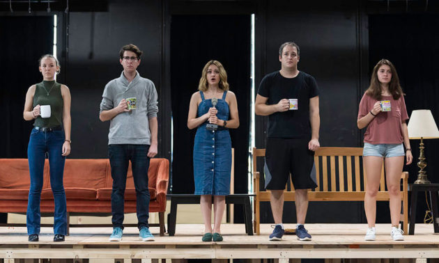 five actors stand on a stage