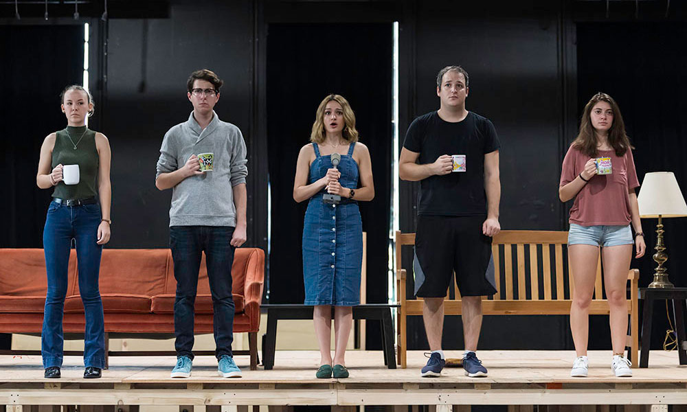 five student actors standing next to each other on stage