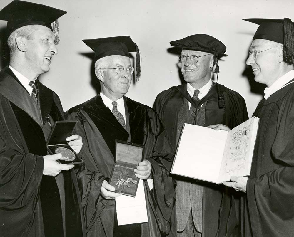 four men in academic robes, one holding a ceremonial set of keys, the other holding a charter.