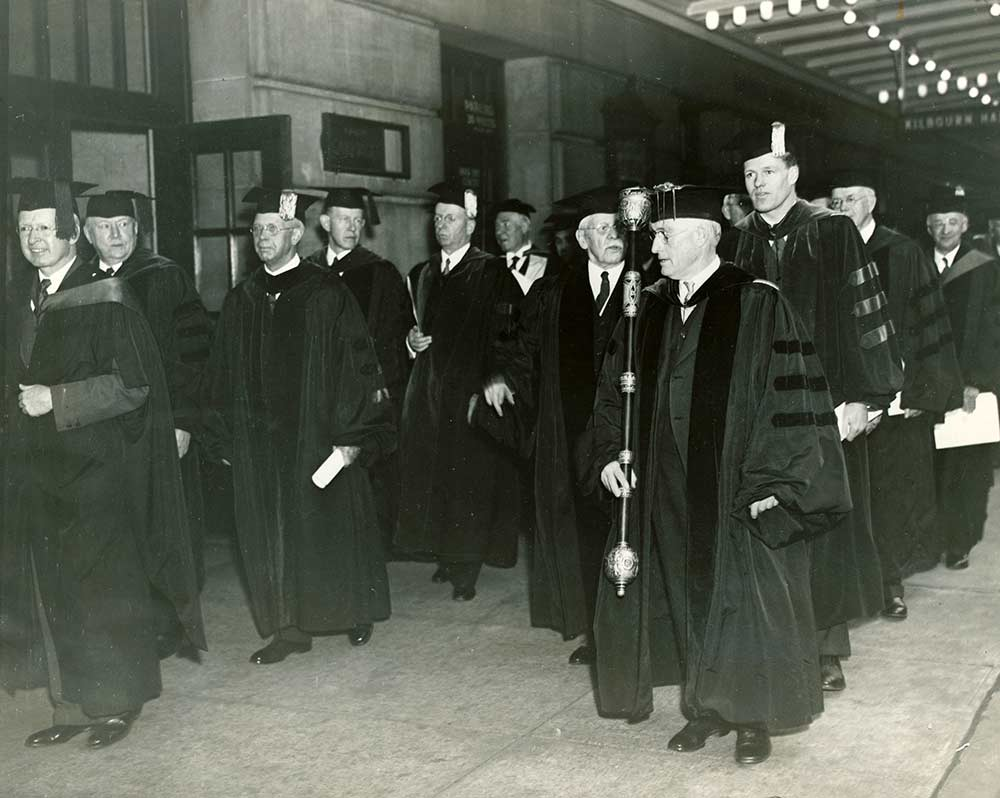 archival photo of procession ofpeople in cap and gown outside Eastman Theatre
