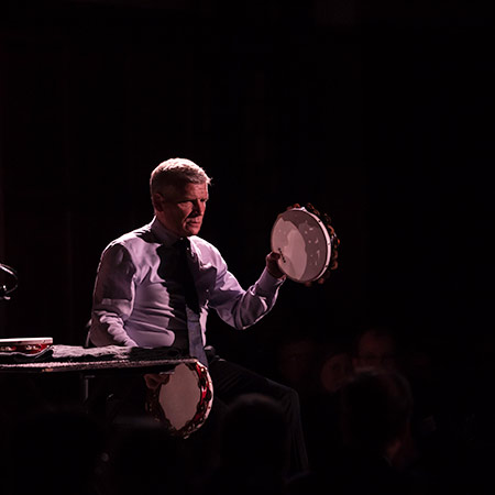 percussionist on stage with two tambourines.