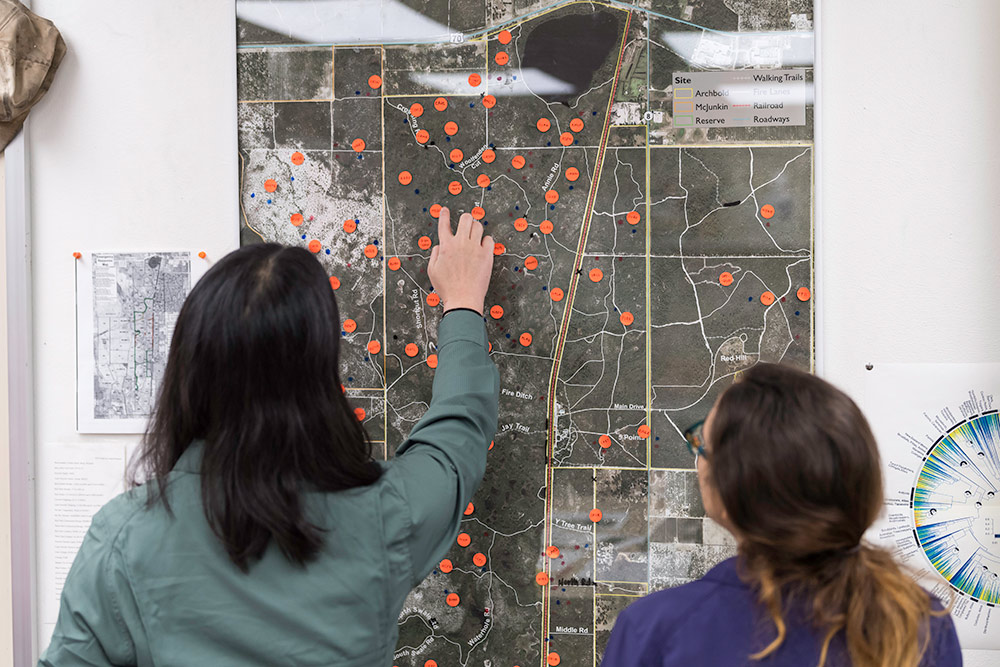 two researchers look at orange dots plotted on a wall map