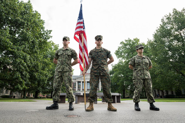 three navy midshipmen standing and holding an American flag in front of Rush Rhees Library