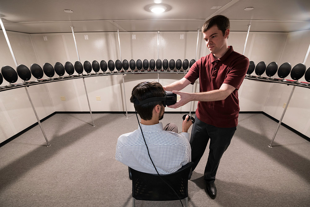 person sitting in a chair wearing a virtual reality headset and surrounded by speakers as another person adjusts the headset