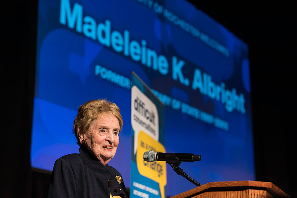 Madeleine Albright on stage in front of a screen that bears her name