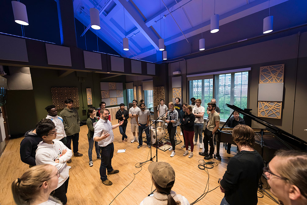 large group of students stands in a circle in recording studio with a piano in the background, listening as a professor teaches.
