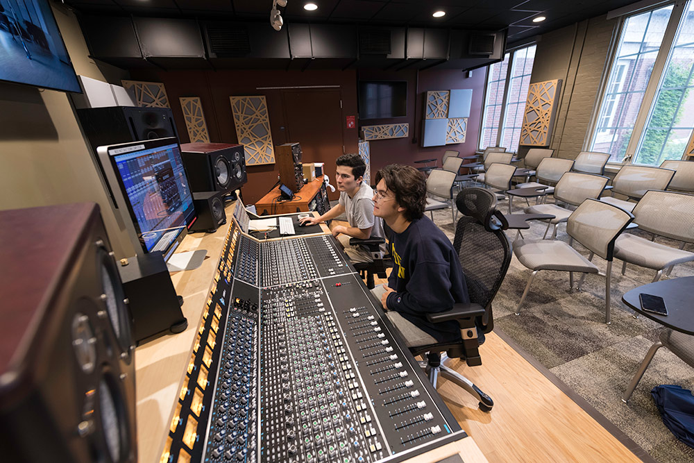 two students sitting behind a large mixing board in a recording studio