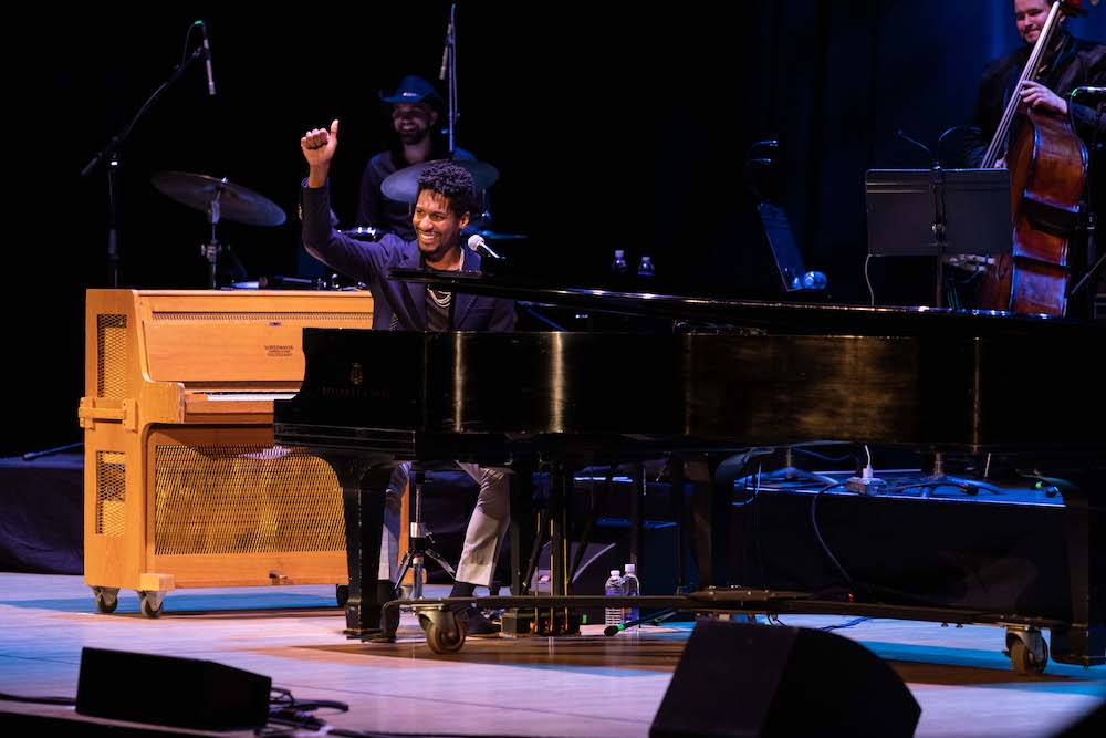 Jon Batiste seated at piano on stage