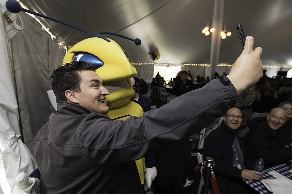 pereson takes a selfie with Rocky mascot