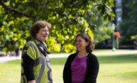 Joan Rubin and Wendi Heinzelman talking and laughing on the quad