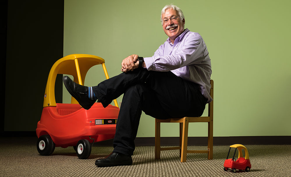 Karl Rosengren smiles while sitting on a chair and surrounded by large and small versions of a child's riding toy.