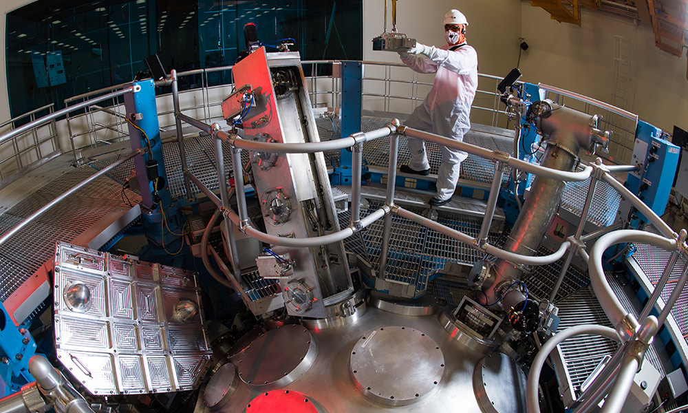 Scientists in clean suits at work in large laser array.