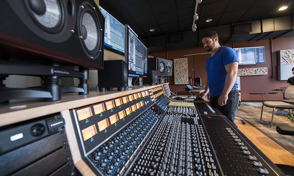 professor stands in front of a large sound board in a recording studio