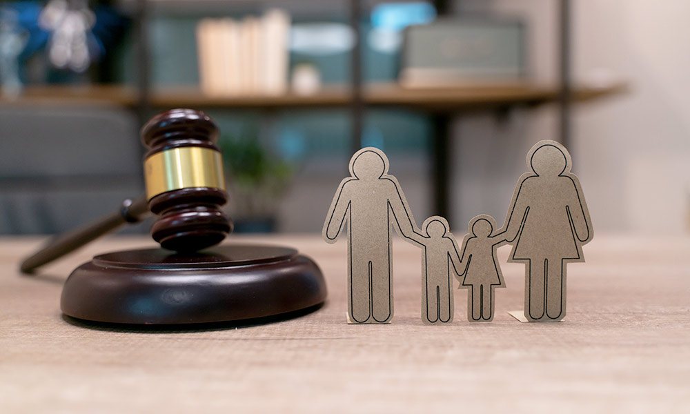 cut out dolls represent a family with two parents and two children, on a desk with a judge's gavel
