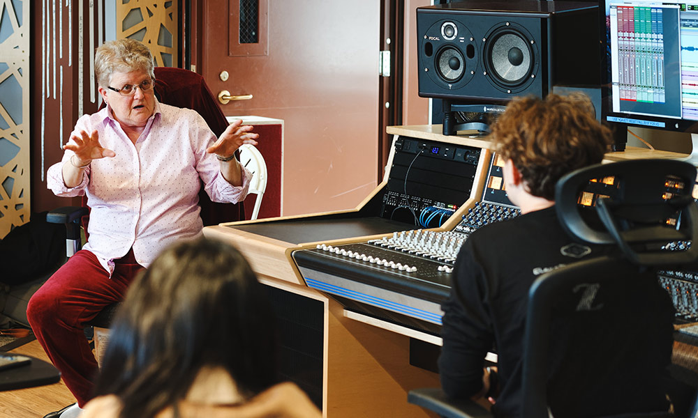 Leslie Ann Jones sitting in front of a control board in a recording studio and speaking to students.