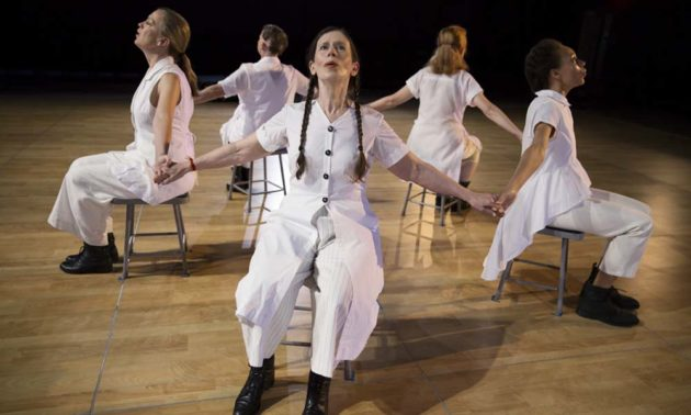 Meredith Monk and four other performers clad in white are seated with their backs to each other while holding hands.