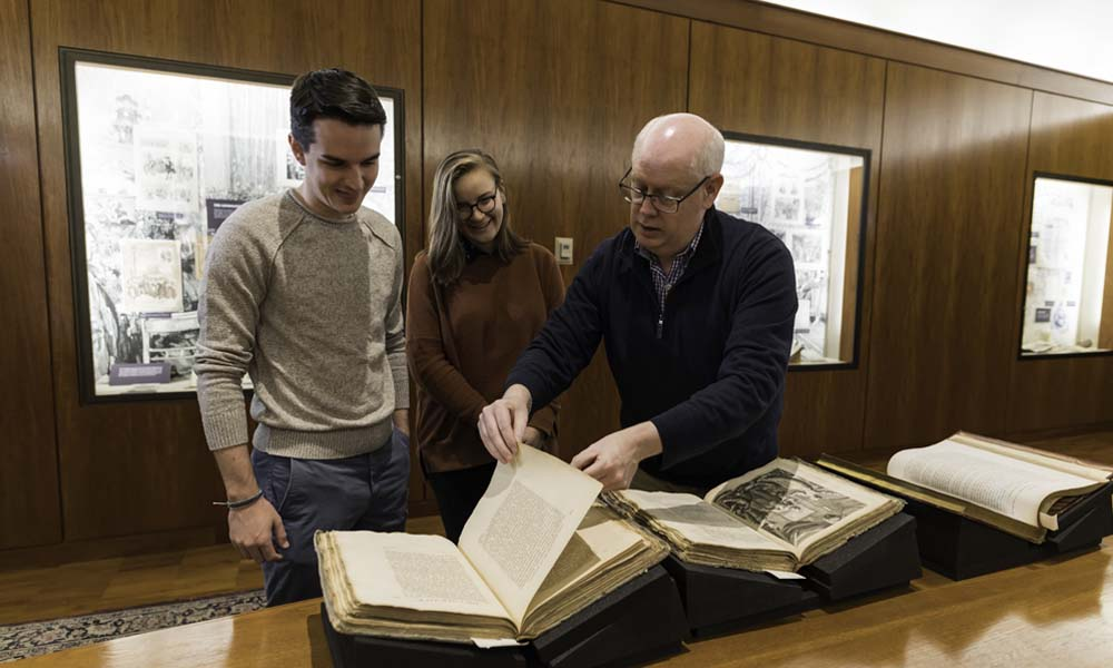 Ryan Prendergast leafs through a manuscript while two students look on.