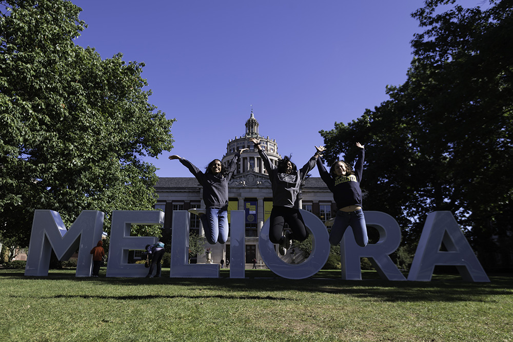 three students jump in front of Meliora letters