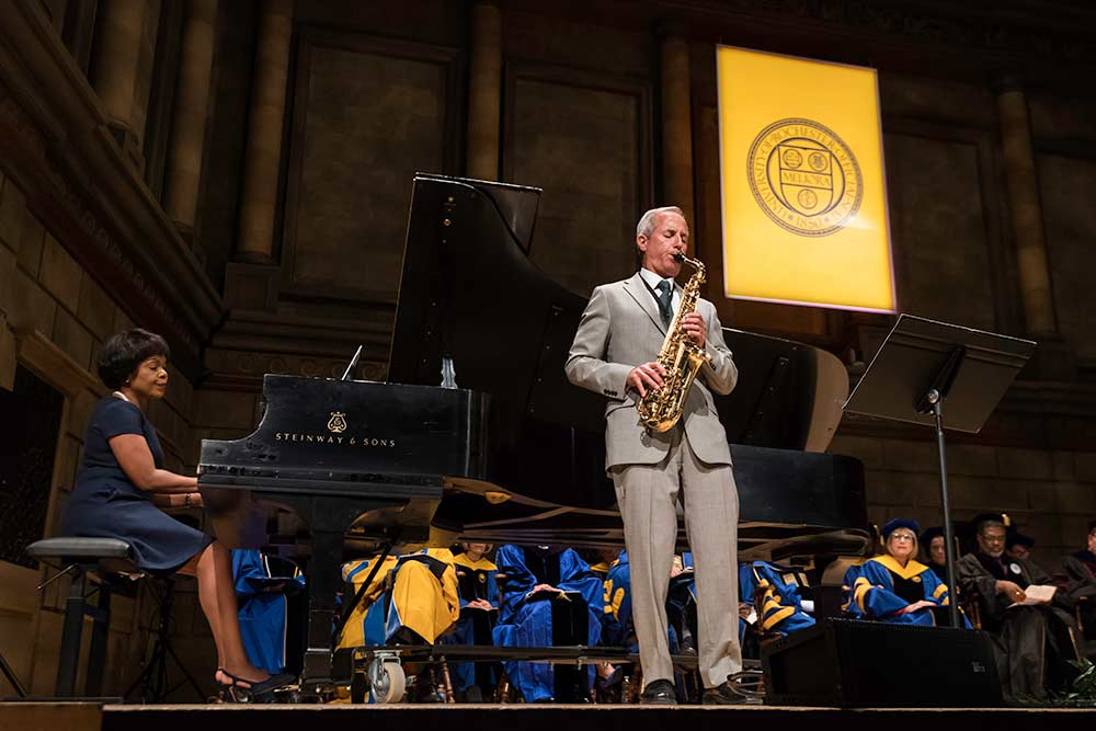 Saxophonist and pianist perform on stage.