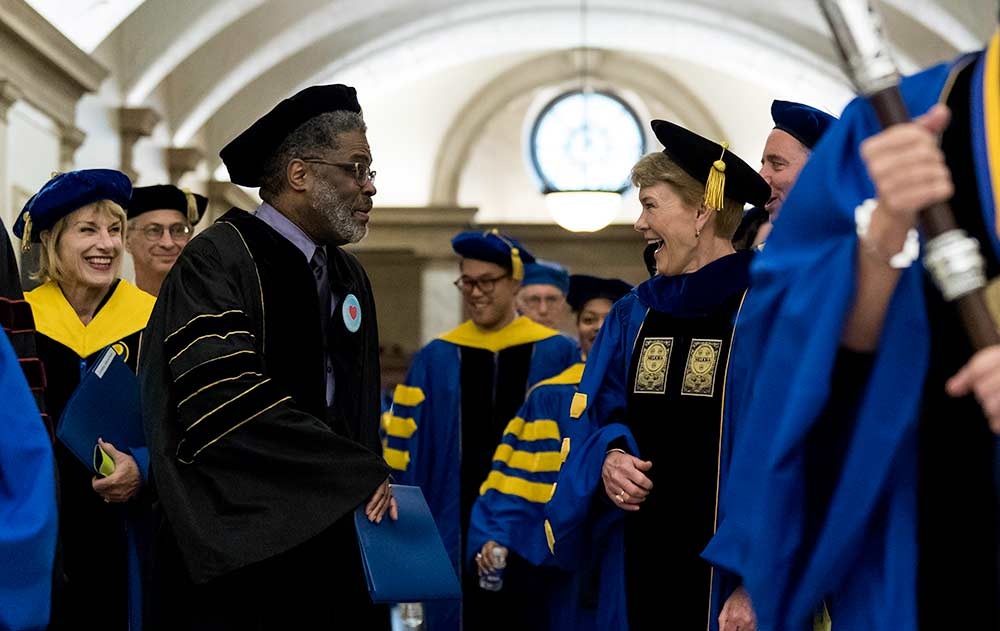 Sarah Mangelsdorf talks and laughs with Wade Norwood as the procession in academic attire leaves Eastman Theatre