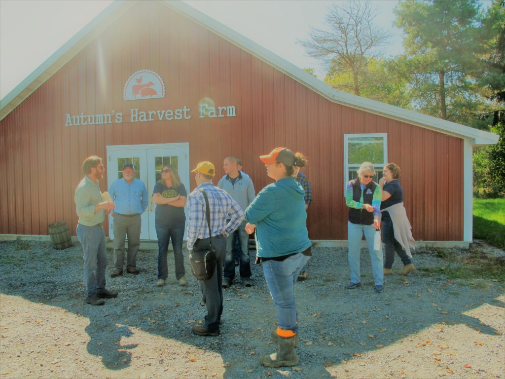 students taking a tour stand in front of a barn painted with a sign that reads Autumn's Harvest Farm