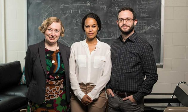portrait of three professors standing in front of a blackboard covered in equations.