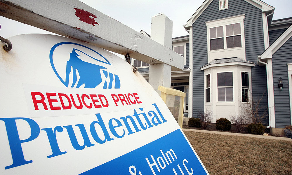 a sign reads FOR SALE REDUCED PRICE outside of what looks like a new home.