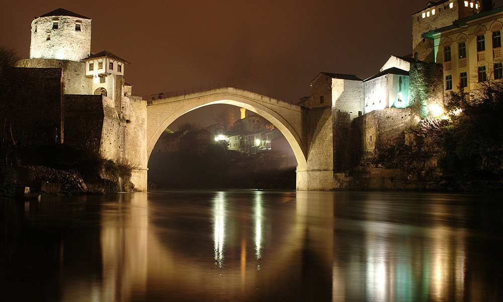 Mostar Bridge lit up at night.